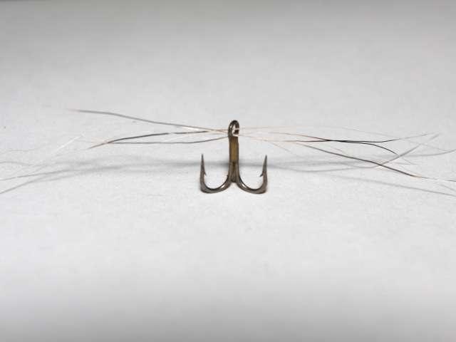 Вставляем барсучью шерсть в ушко крючка